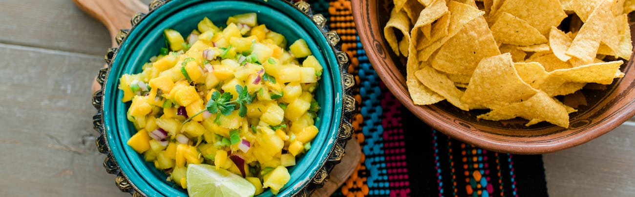 Pineapple Mango Salsa in a turquoise bowl and chips on the side