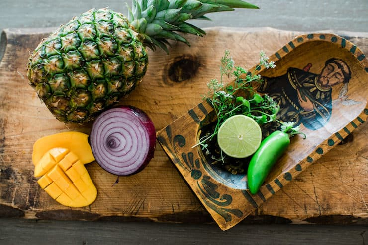 overhead shot of ingredients needed to make pineapple mango salsa recipe on a wooden board