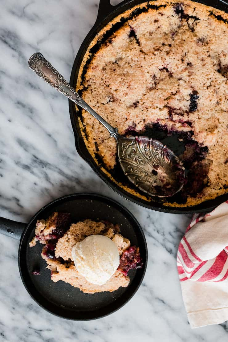 This warm, comforting, and buttery berry cobbler is a simple, scrumptious dessert featuring plump, tart berries in a tender sweet cake topped with a scoop of vanilla ice cream.