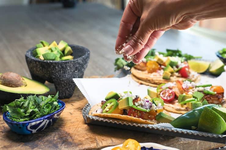 Sprinkling Shrimp Tacos with queso fresco, having chopped avocado and cilantro on the side