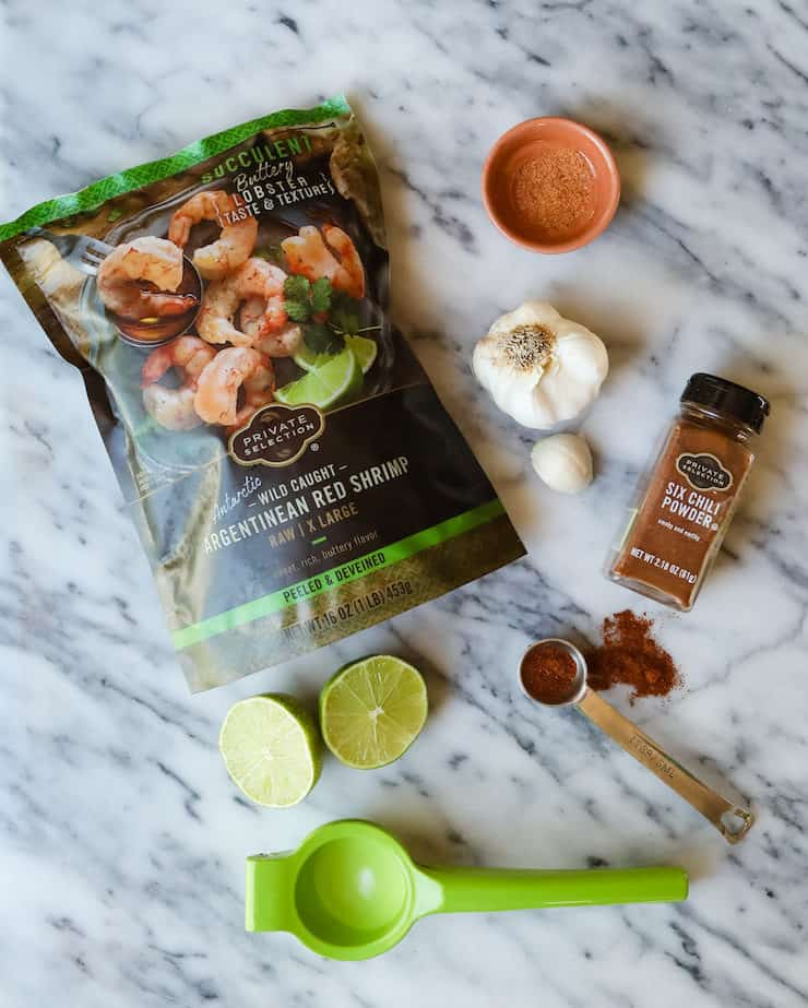 frozen shrimp, garlic, lime and chili powder on a marble table with a lime squeezer