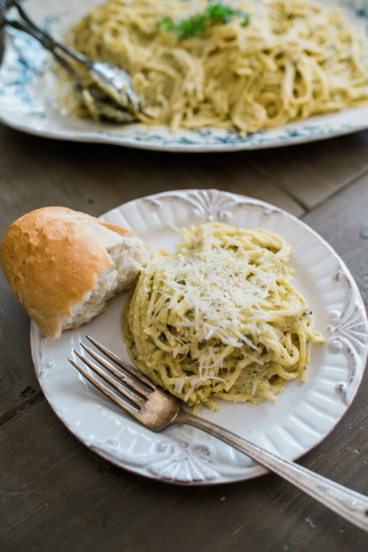 serving of Espagueti Verde (Spaghetti with Creamy Poblano Sauce) on a white plate with a piece of bread