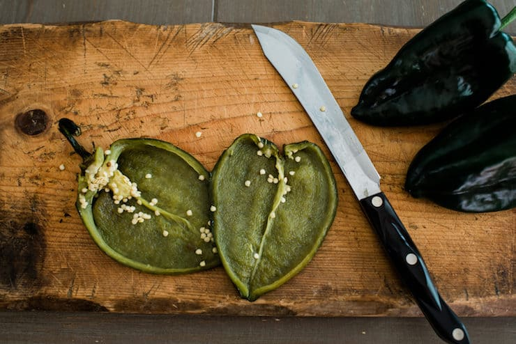 roasted poblano pepper on a cutting board sliced in half lengthwise