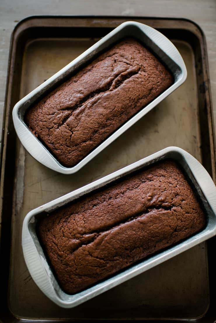 two bread loaf pans with baked chocolate breads on a sheet pan