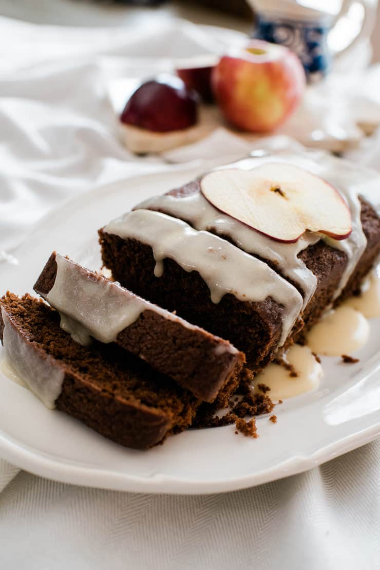 sliced chocolate apple bread drizzled with a sweet boozy bourbon glaze on a white plate with apples in the background