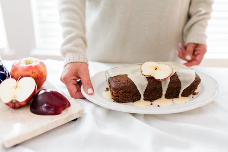 a chocolate bread drizzled with bourbon glaze with apples on the table