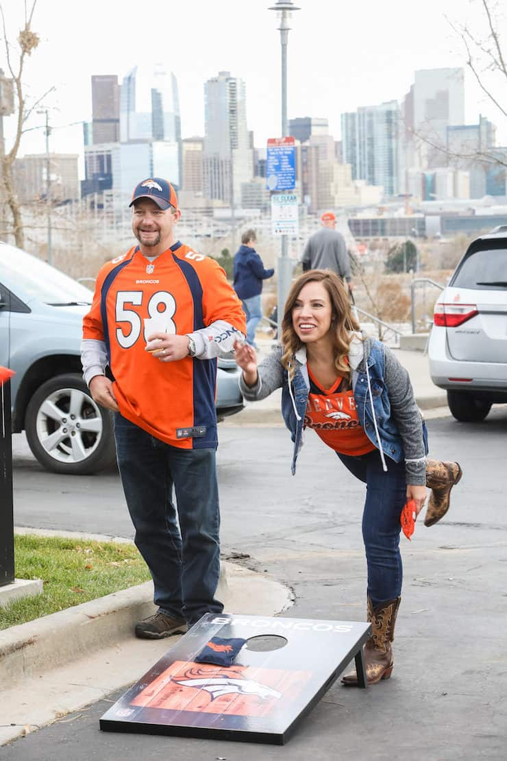 guy and girl playing cornhole at a Denver Broncos tailgate