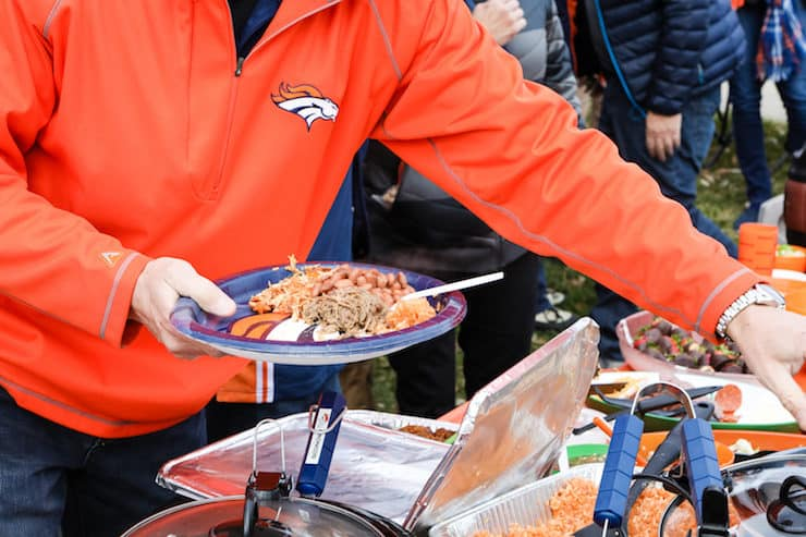 holding a Denver Broncos paper plate with tailgate food
