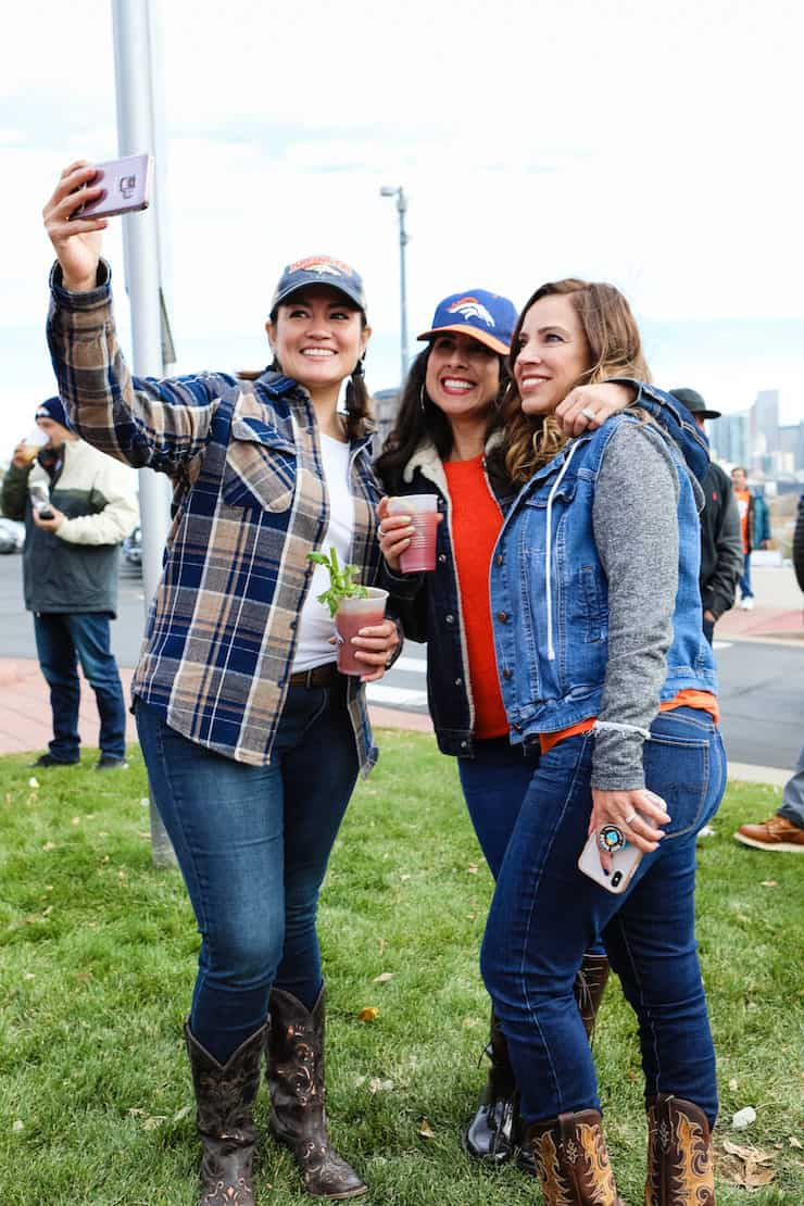 three Latina girls taking a selfie at a Denver broncos tailgate holding Bloody Marys