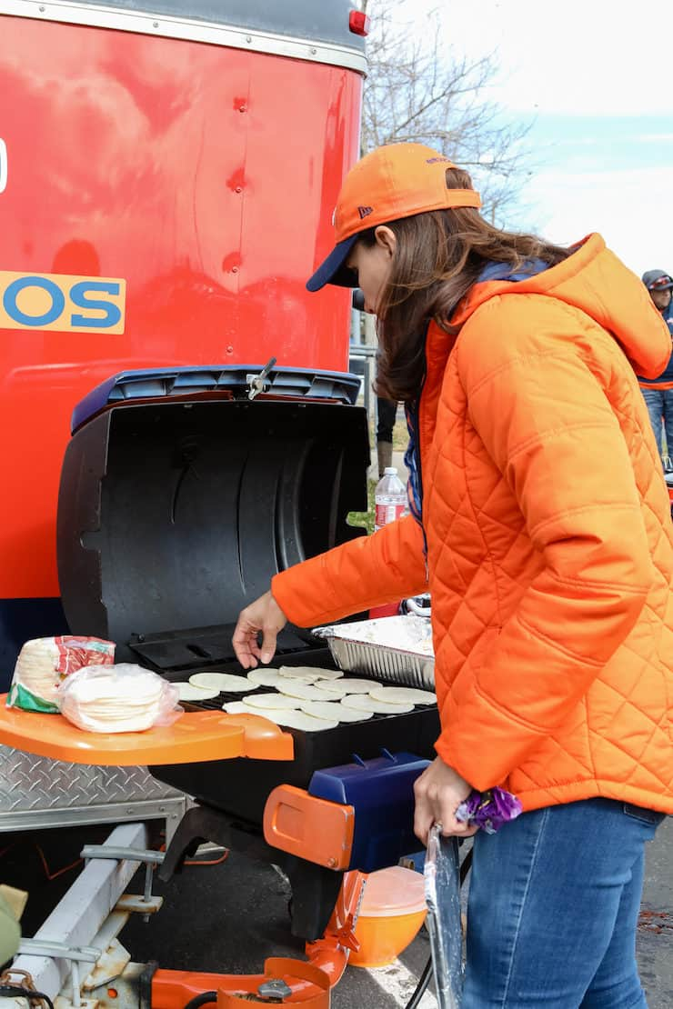 Denver Broncos tailgate girl grilling tortillas for taco bar