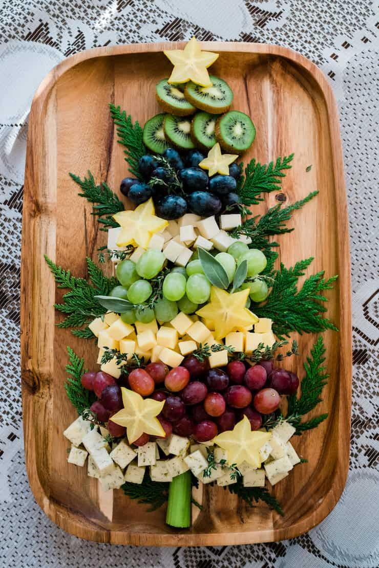 Christmas tree shaped cheese platter on a wooden tray kiwi grapes star fruit and cheese surrounded by evergreen branches