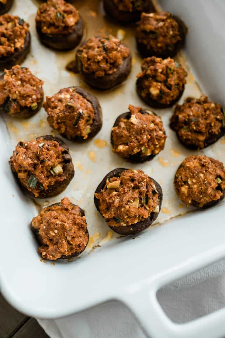 close up of stuffed chorizo mushrooms in a white baking dish