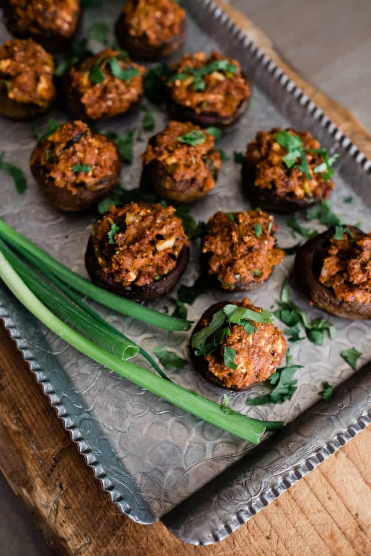 stuffed mushrooms sprinkled with cilantro on a silver tray with scallions on the side