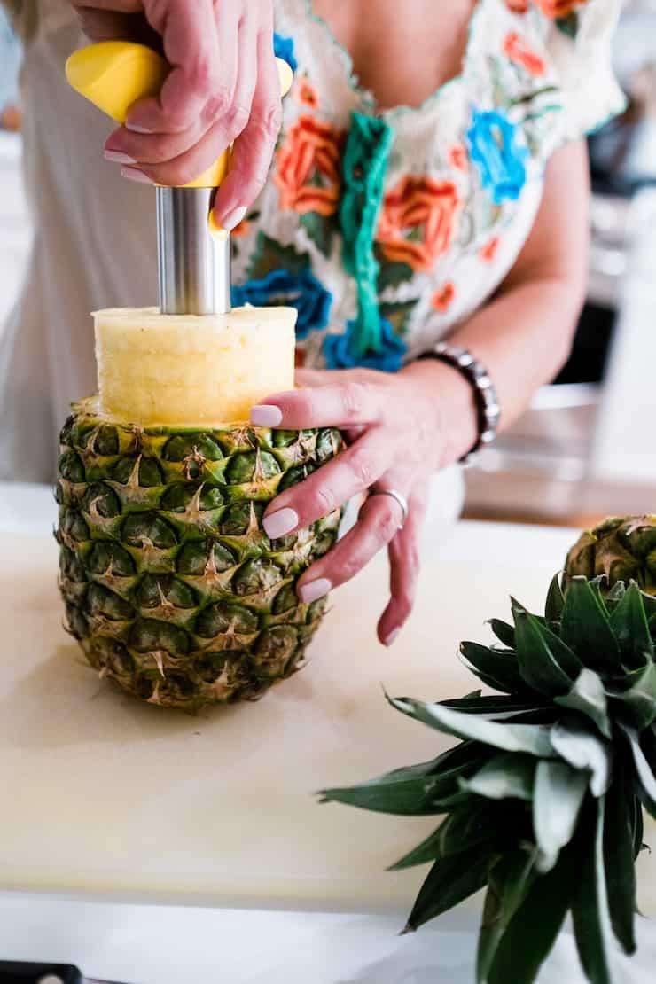 woman using pineapple corer tool on fresh pineapple