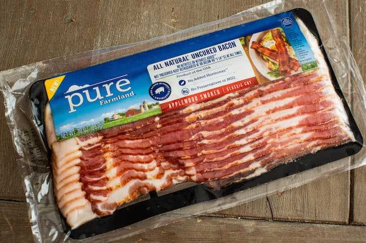 Pure Farmland all natural uncured bacon packed on a big wooden table