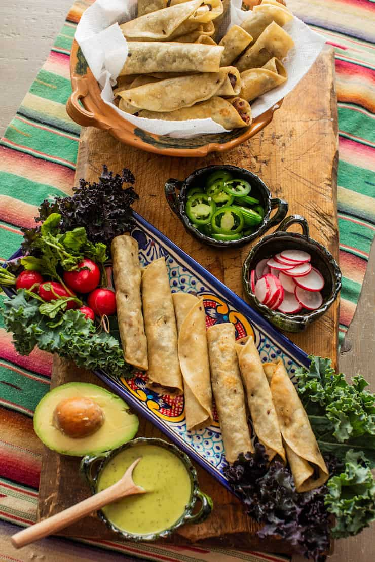 Mouthwaterting Black Bean, Kale and Bacon Flautas ready for a party with jalapeño, radish, avocado and sauce on the side