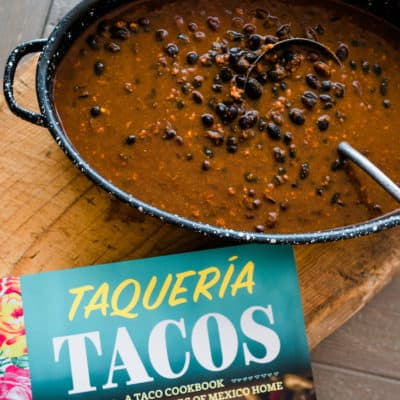 Frijoles Adobados ready in a big dish with Taqueria Tacos cookbook right next to it on a big wooden board