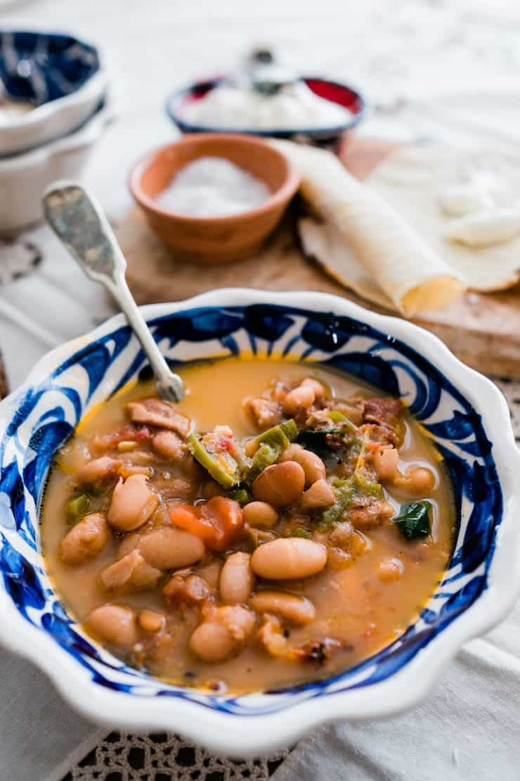 Blue and white bowl filled with pinto beans called frijoles charros