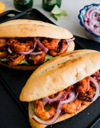two shrimp tortas on a black plate