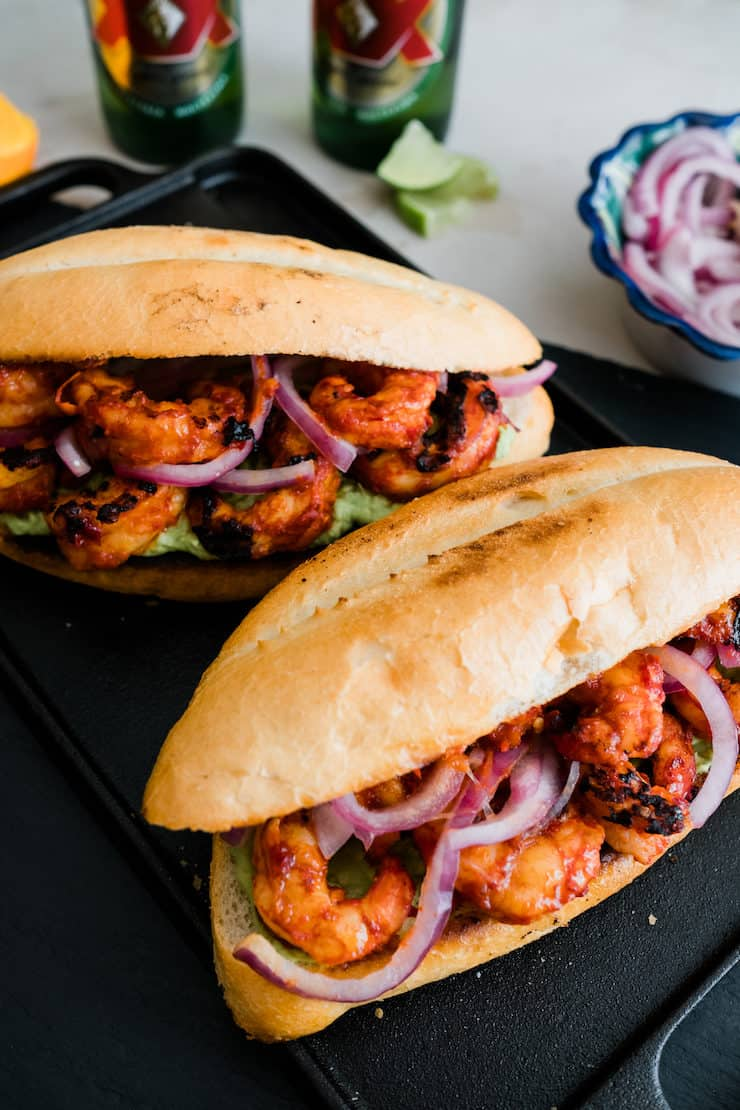 two spicy shrimp tortas on a black plate