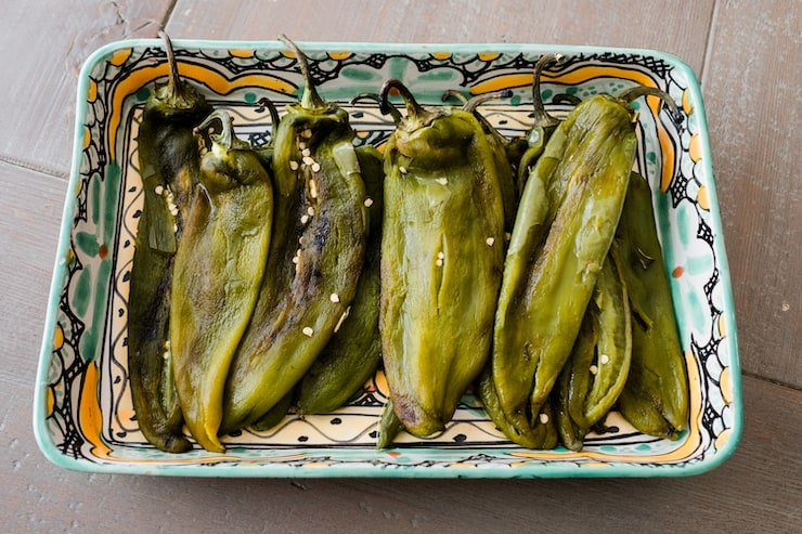 peeled, fire roasted chiles on a painted ceramic tray