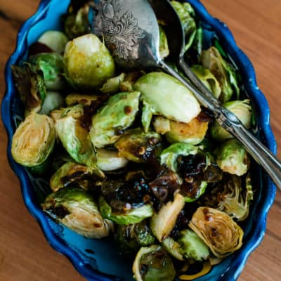 Maple Syrup Chipotle Roasted Brussels Sprouts side dish served in a beautiful blue plate