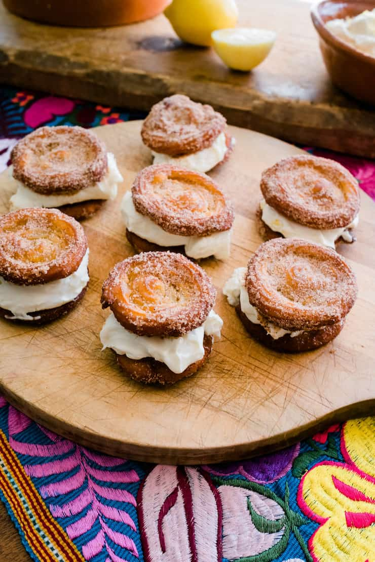 Serving delicious Churro Lemon Cream Sandwiches on a wooden board with lemon in the background