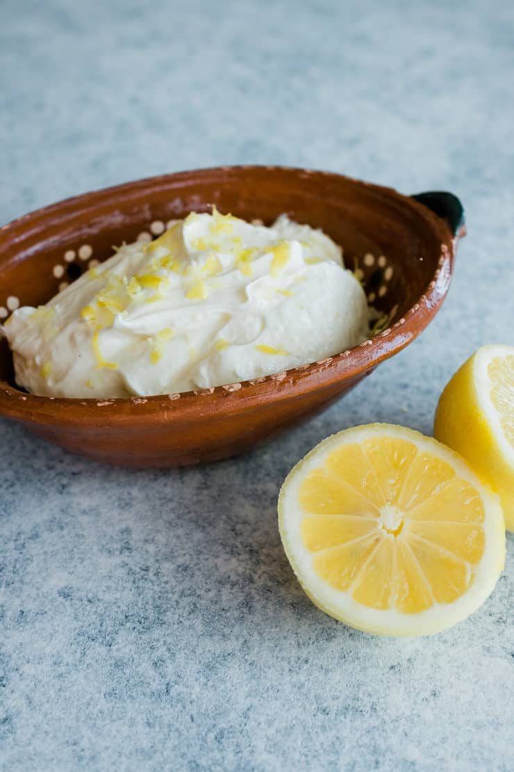 Homemade lemon whipped cream frosting with two halves of lemon