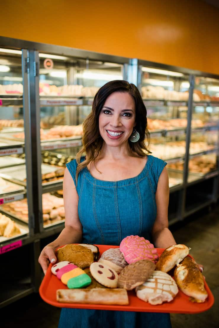 Mexican pan dulce from A to Z Latina food blogger in a Mexican panderia bakery holding a tray of sweet bread