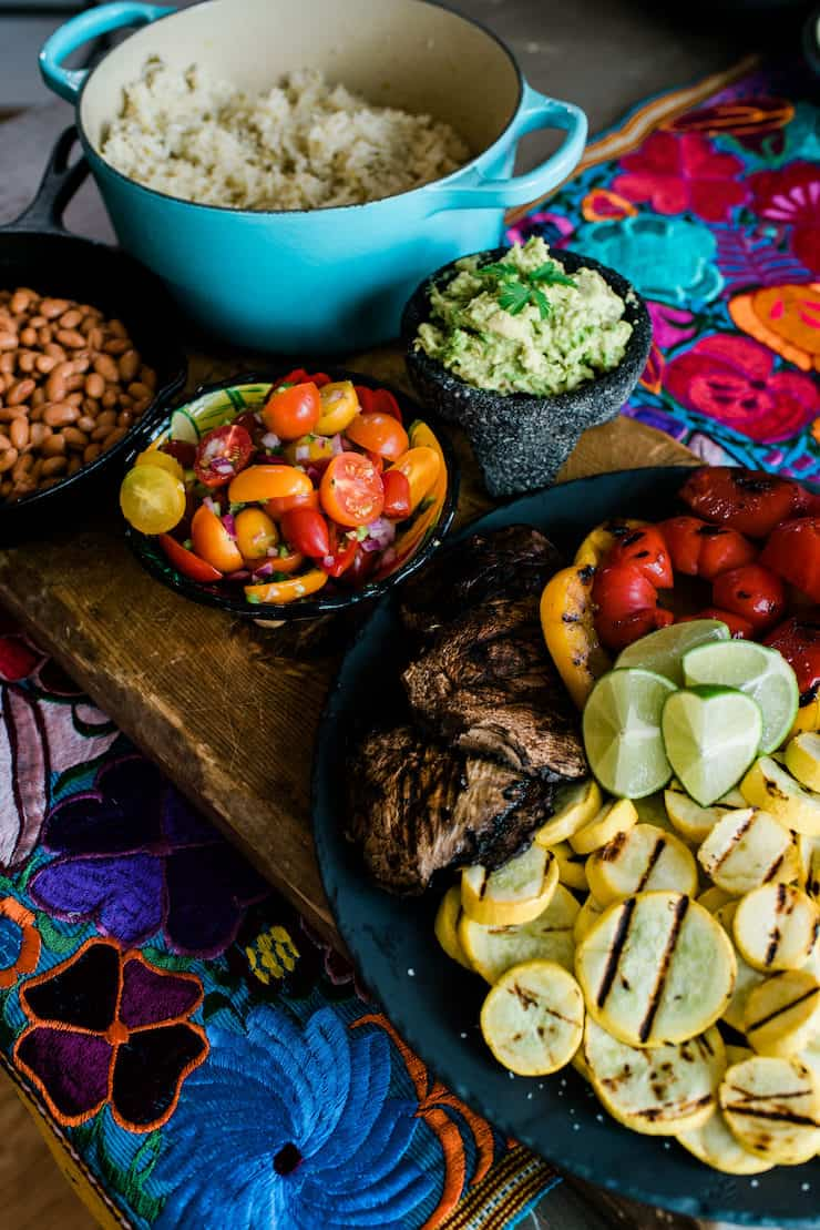 wooden table topped with ingredients to assemble burrito bowls - grilled veggies, pico de gallo, guacamole, frijoles de la olla and hatch green chile rice
