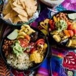 two plated burrito bowls on a colorful tapestry lined table