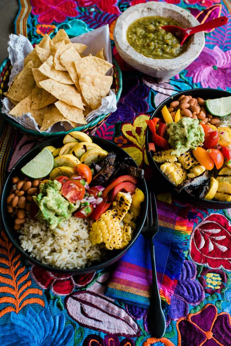 overhead shot of two assembled vegan burrito bowls on a colorful tapestry with a bowl of tortilla chips and green salsa on the side.