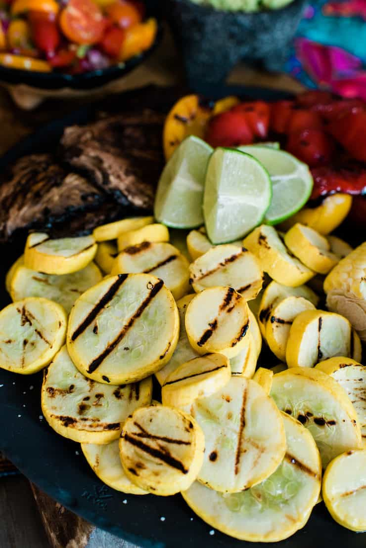 black plate with grilled summer squash, bell peppers and mushrooms