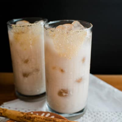 Two glasses filled with ice and horchata with tequila