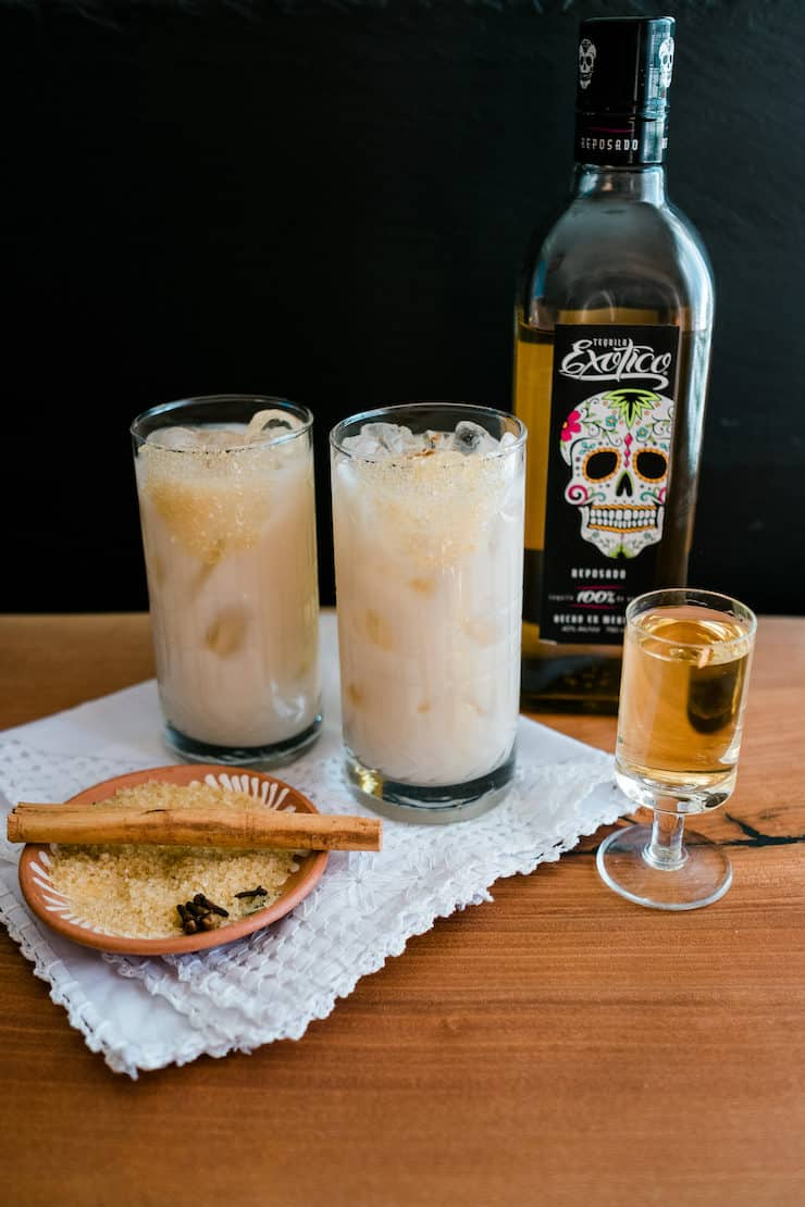 Two glasses filled with horchata and a bottle of Exotico tequila against a black background