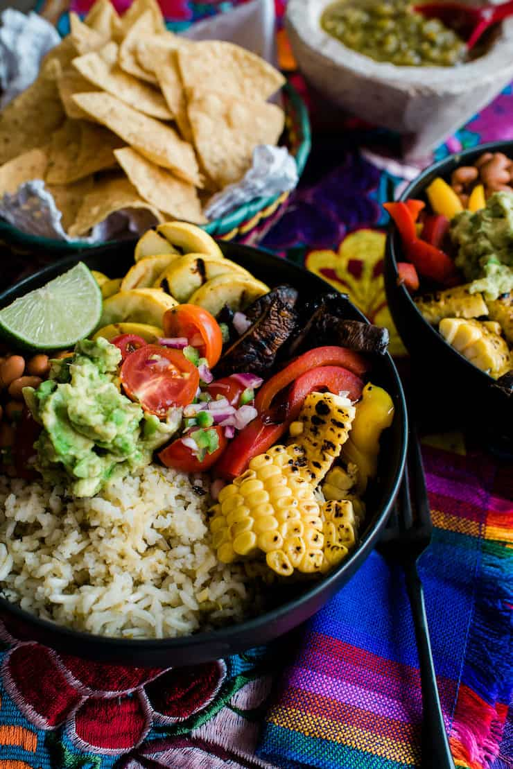 close up shot of a grilled veggie vegan burrito bowl with a basket of chips in the background