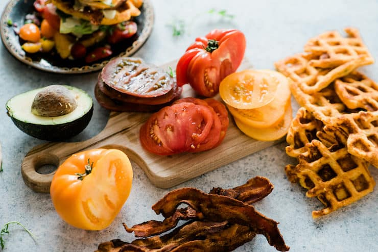 wooden cutting board with sliced heirloom tomatoes, half an avocado, crispy bacon, and cornmeal waffles. An assembled BLT Waffle is blurred in the back of the image.