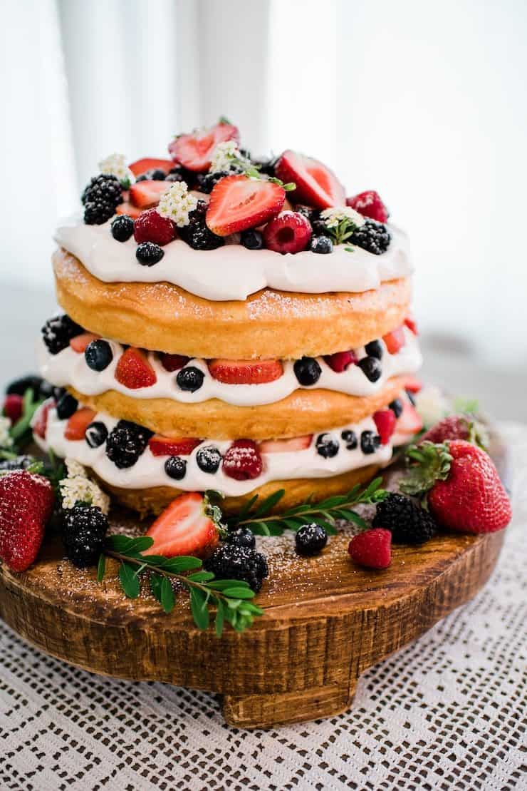 three layer naked cake topped with whipped cream and fresh berries