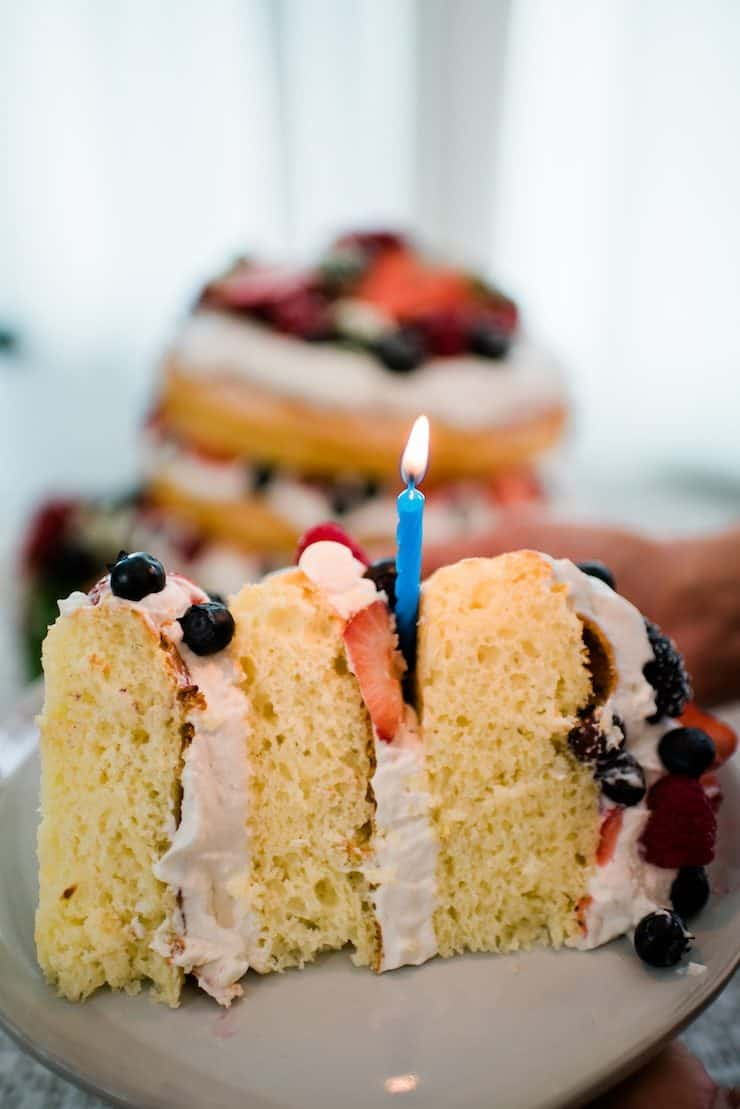 Lemon Buttermilk Spring Fling Cake sliced with a birthday candle
