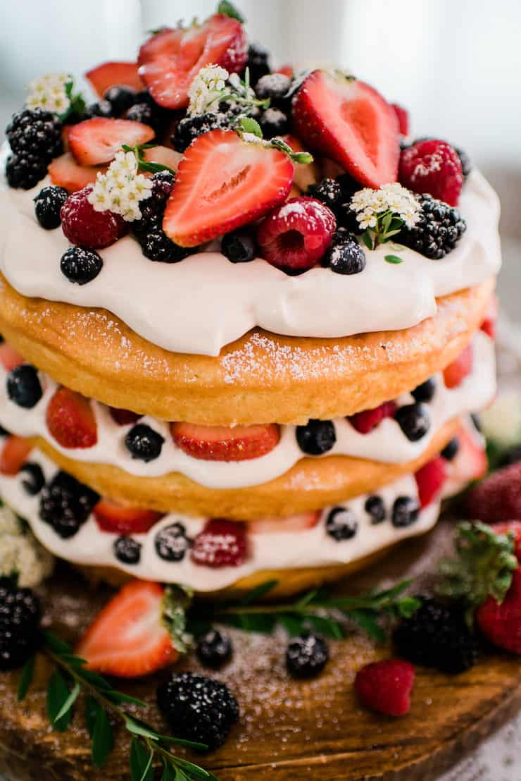 Lemon Buttermilk Naked Cake topped with whipped cream and berries