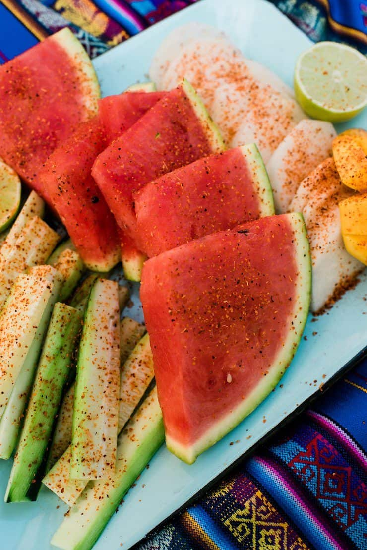 fruit slices sprinkled with chili powder on a teal platter on a Mexican runner