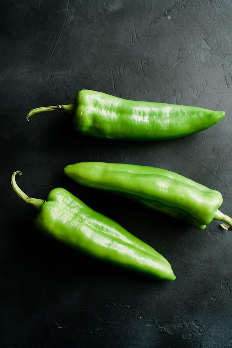 three Anaheim Chile peppers on a black background