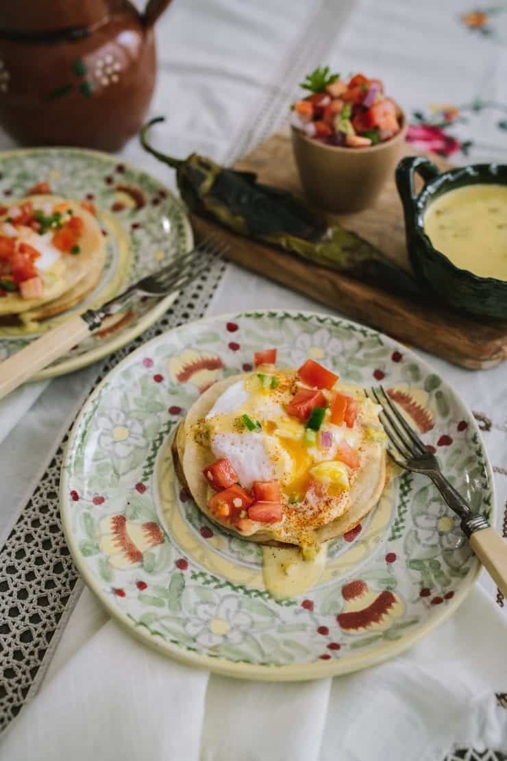Poached, free-range eggs served on a stack of lightly fried, crispy corn tortillas drizzled with roasted green chile hollandaise sauce and pico de gallo