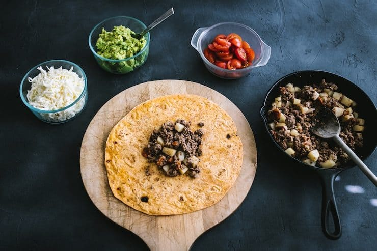 cheese, guacamole and tomato in bowls, picadillo beef in cast iron skillet, and tortilla on wooden board with some picadillo in the center to make homemade Crunchwraps