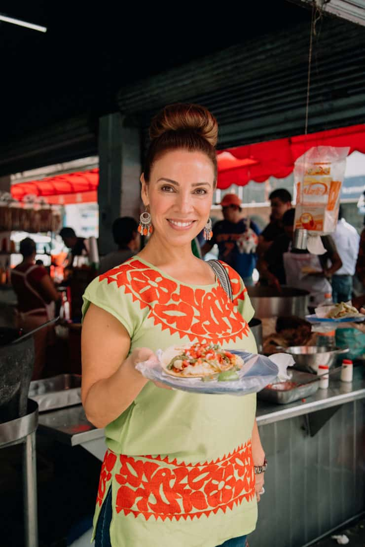 food and travel blogger Latina Yvette Marquez in Mexico City holding a plate of tacos wearing a colorful embroidered green and orange Mexican blouse