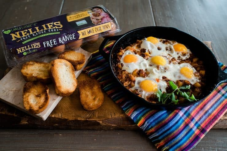 Baked Eggs with Chorizo and Potatoes and toasted bolillo slices with a carton of eggs