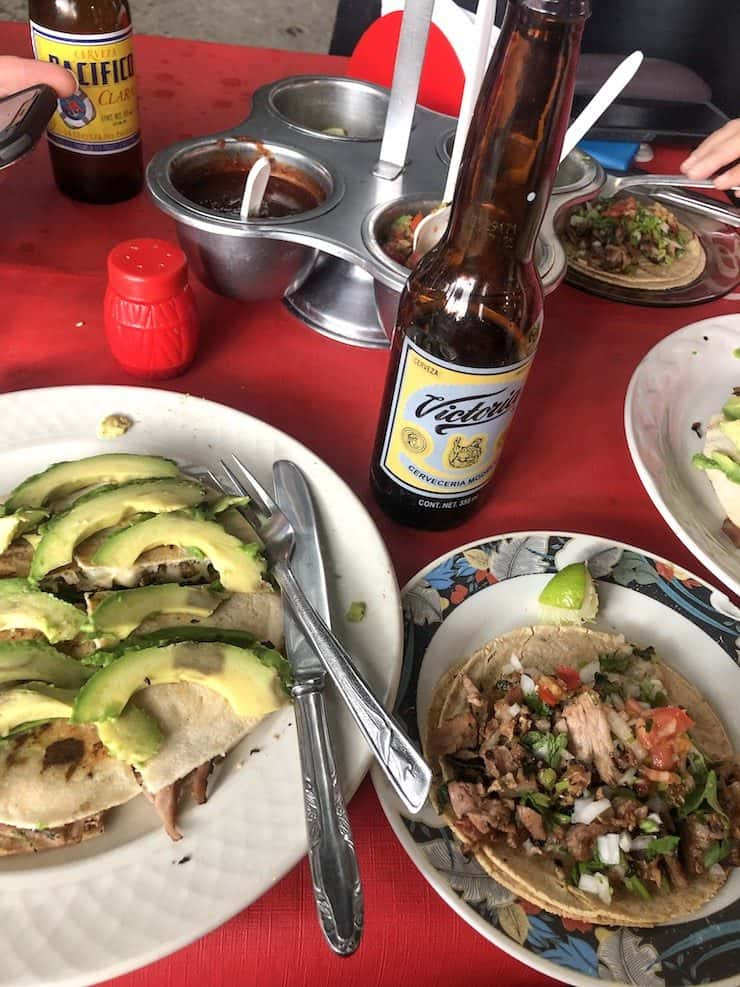 Table full of tacos and Mexican beer at Taqueria El Greco