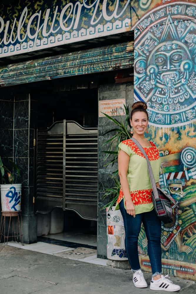 Food and travel Latina blogger standing in front of a colorful wall in Mexico City