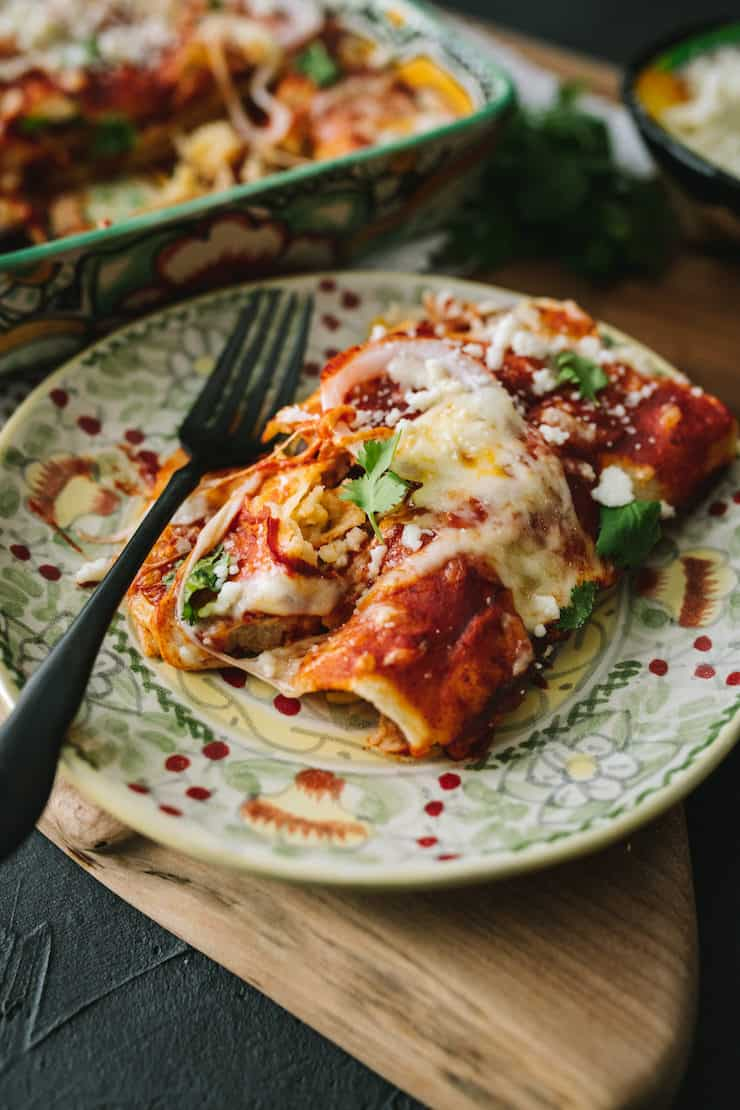 red Black Bean & Rice Enchiladas rolled served on a Mexican talabera plate with a black fork