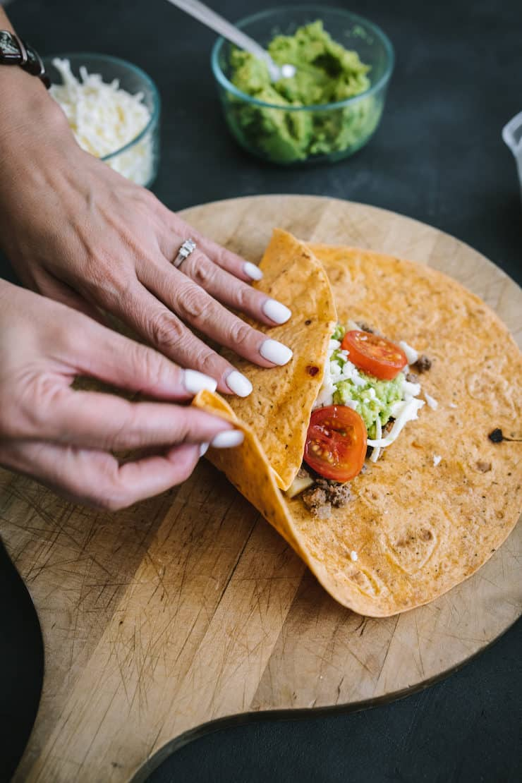 two hands beginning to fold a homemade crunchwrap on a wooden board